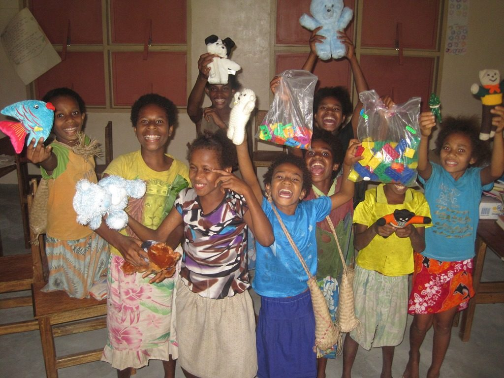 Kids holding toys from the Kiwanis donation